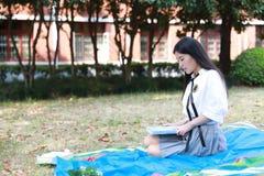 Το ευτυχές ασιατικό κινεζικό όμορφο κοστούμι σπουδαστών ένδυσης κοριτσιών διαβασμένο στο σχολείο βιβλίο κάθεται στη χλόη στοκ φωτογραφίες