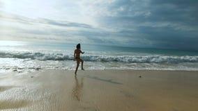 Το ευτυχές λατρευτό κορίτσι στο μαύρο μπικίνι πηδά και τρέχει κατά μήκος της παραλίας της από το Μπαλί ακτής Νέος θηλυκός ταξιδιώ απόθεμα βίντεο