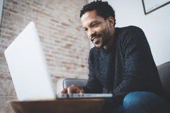 Το ευτυχές αφρικανικό άτομο έντυσε στο γκρίζο πουλόβερ και τη δακτυλογράφηση στο lap-top, χαμογελώντας καθμένος τον καναπέ ανασκό Στοκ Φωτογραφίες
