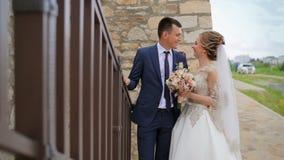 Το ευτυχές γαμήλιο ζεύγος εξετάζει το ένα το άλλο κοντά σε μια όμορφη σκάλα Ηλιόλουστη ημέρα γάμου απόθεμα βίντεο