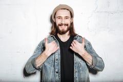Το ευτυχές γενειοφόρο άτομο hipster κάνει τους αντίχειρες επάνω στη χειρονομία Στοκ Εικόνες