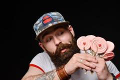 Το ευτυχές γενειοφόρο βάναυσο άτομο σε μια μοντέρνη ΚΑΠ κρατά ένα πακέτο των καραμελών lollipops στοκ εικόνες