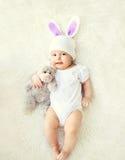Το ευτυχές γλυκό μωρό στο πλεκτό καπέλο με τα αυτιά κουνελιών και teddy αφορά το κρεβάτι Στοκ Φωτογραφίες