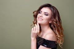 Το ευτυχές ευχαριστημένο θηλυκό με το θετικό χαμόγελο, χαμόγελα ευρέως, έντυσε στο μαύρο φόρεμα με τα τσέκια, πέρα από τον πράσιν στοκ εικόνα με δικαίωμα ελεύθερης χρήσης