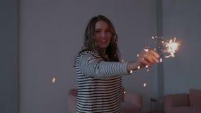 Το ευτυχές εύθυμο κοίταγμα κοριτσιών στη κάμερα, που κινείται στο σκοτεινό δωμάτιο και τα κυματίζοντας πυροτεχνήματα λαμπιρίζει σ απόθεμα βίντεο
