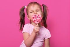 Το ευτυχές εύθυμο χαριτωμένο κορίτσι φορά αυξήθηκε τ hirt, στάσεις που α στοκ φωτογραφίες