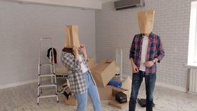 Το ευτυχές ζεύγος έχει τη διασκέδαση στο νέο διαμέρισμά τους με τις τσάντες χαρτονιού στα κεφάλια τους φιλμ μικρού μήκους
