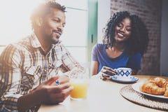 Το ευτυχές ζεύγος αφροαμερικάνων έχει το πρόγευμα μαζί το πρωί στον ξύλινο πίνακα Νέος μαύρος και δικοί του Στοκ εικόνες με δικαίωμα ελεύθερης χρήσης