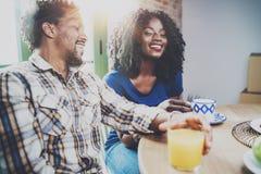 Το ευτυχές ζεύγος αφροαμερικάνων έχει το πρόγευμα μαζί το πρωί στον ξύλινο πίνακα Νέος μαύρος και δικοί του Στοκ εικόνα με δικαίωμα ελεύθερης χρήσης