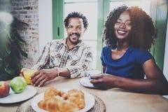 Το ευτυχές ζεύγος αφροαμερικάνων έχει το πρόγευμα μαζί το πρωί στον ξύλινο πίνακα Χαμογελώντας μαύρος και δικοί του Στοκ φωτογραφία με δικαίωμα ελεύθερης χρήσης
