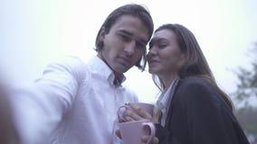 Το ευτυχές ζεύγος κάνει selfie τον τύπο καφέ κατανάλωσης υπαίθρια και ο χρόνος εξόδων φίλων συνδέει μαζί ερωτευμένο ευτυχή φιλμ μικρού μήκους