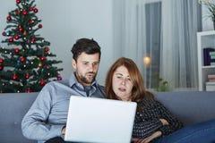 Το ευτυχές ζεύγος κοιτάζει στο PC lap-top για τα Χριστούγεννα στοκ φωτογραφία