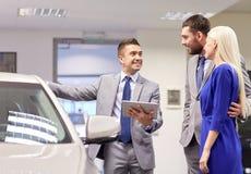 Το ευτυχές ζεύγος με τον έμπορο αυτοκινήτων στο αυτοκίνητο παρουσιάζει ή σαλόνι Στοκ Εικόνες