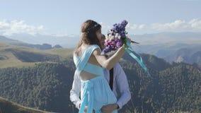 Το ευτυχές ζεύγος περιστρέφει στα όπλα στο υπόβαθρο των βουνών απόθεμα βίντεο