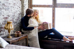 Το ευτυχές ζεύγος των εραστών στα πουλόβερ δίνει σε μεταξύ τους το κάθισμα δώρων στοκ φωτογραφίες