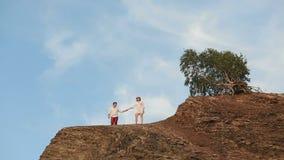 Το ευτυχές ζεύγος των τουριστών κρατά τα χέρια και φιλά στο βράχο Άποψη από Copter απόθεμα βίντεο
