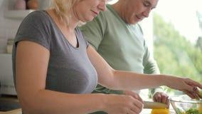 Το ευτυχές ηλικίας οικογενειακό ζεύγος που μαγειρεύει το υγιές μεσημεριανό γεύμα στο διαμέρισμα φιλμ μικρού μήκους