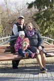 Το ευτυχές ηλικιωμένο ζεύγος με την εγγονή κάθεται σε έναν πάγκο στο θόριο Στοκ Εικόνα