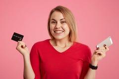 Το ευτυχές θηλυκό πρότυπο χαίρεται να πάρει το μισθό, κρατά την πλαστική κάρτα και το σύγχρονο έξυπνο τηλέφωνο, πηγαίνοντας να ελ στοκ εικόνες