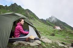 Το ευτυχές θηλυκό τουριστών κάθεται στη σκηνή κοντά στο ρεύμα βουνών Στοκ φωτογραφία με δικαίωμα ελεύθερης χρήσης