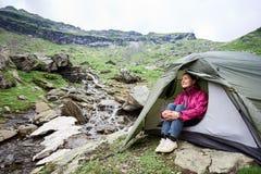 Το ευτυχές θηλυκό τουριστών κάθεται στη σκηνή κοντά στο ρεύμα βουνών Στοκ εικόνα με δικαίωμα ελεύθερης χρήσης
