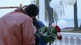 το ευτυχές και αμήχανο κορίτσι αγκαλιάζει έναν τύπο κατά μια ρομαντική ημερομηνία απόθεμα βίντεο