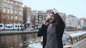 Το ευτυχές καυκάσιο άτομο περπατά και μιλά στο τηλέφωνο 4K Συγκινημένος δημιουργικός τουρίστας που μοιράζεται τις συγκινήσεις στη φιλμ μικρού μήκους