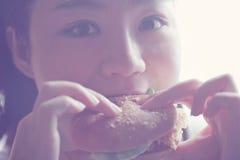 Το ευτυχές κινεζικό κορίτσι ομορφιάς τρώει την κινηματογράφηση σε πρώτο πλάνο χάμπουργκερ, κενό άσπρο υπόβαθρο Στοκ Φωτογραφίες