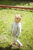Το ευτυχές κοκκινομάλλες κορίτσι Lilittle στέκεται κάτω από τον όμορφο θερινό ήλιο στην παιδική χαρά στοκ φωτογραφία