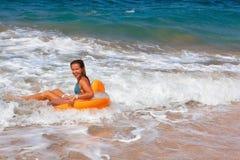 Το ευτυχές κορίτσι έχει τη διασκέδαση στην κυματωγή θάλασσας στην παραλία στοκ εικόνες