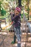 Το ευτυχές κορίτσι, γυναίκες, που αναρριχείται στο εργαλείο σε ένα πάρκο περιπέτειας συμμετέχει στην αναρρίχηση βράχου στο δρόμο  στοκ εικόνα με δικαίωμα ελεύθερης χρήσης
