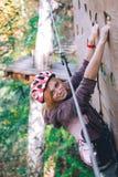 Το ευτυχές κορίτσι, γυναίκες, που αναρριχείται στο εργαλείο σε ένα πάρκο περιπέτειας συμμετέχει στην αναρρίχηση βράχου στο δρόμο  στοκ φωτογραφίες