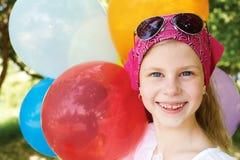 Το ευτυχές κορίτσι είναι σε ένα λούνα παρκ με τα ζωηρόχρωμα μπαλόνια Στοκ Φωτογραφία