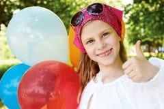 Το ευτυχές κορίτσι είναι σε ένα λούνα παρκ με τα ζωηρόχρωμα μπαλόνια Στοκ Εικόνες