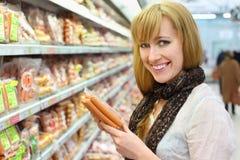 Το ευτυχές κορίτσι επιλέγει το λουκάνικο στο κατάστημα στοκ φωτογραφία με δικαίωμα ελεύθερης χρήσης