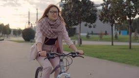 Το ευτυχές κορίτσι εφήβων οδηγεί ένα ποδήλατο σε ένα πάρκο στο λυκόφως απόθεμα βίντεο