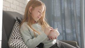 Το ευτυχές κορίτσι κερδίζει χρήματα στη piggy τράπεζα στο σπίτι της Παιδί που παρεμβάλλει ένα νόμισμα σε μια piggy τράπεζα, εσωτε απόθεμα βίντεο