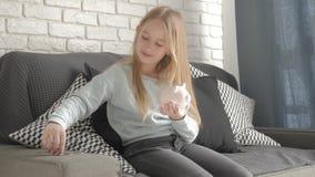 Το ευτυχές κορίτσι κερδίζει χρήματα στη piggy τράπεζα στο σπίτι της Παιδί που παρεμβάλλει ένα νόμισμα σε μια piggy τράπεζα, εσωτε φιλμ μικρού μήκους