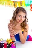 Το ευτυχές κορίτσι κομμάτων με παρουσιάζει την κατανάλωση της σοκολάτας Στοκ Φωτογραφίες