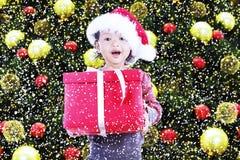 Το ευτυχές κορίτσι λαμβάνει το δώρο Χριστουγέννων κάτω από το δέντρο Στοκ εικόνα με δικαίωμα ελεύθερης χρήσης