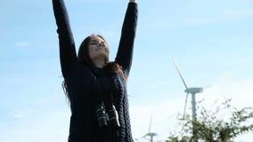 Το ευτυχές κορίτσι παίρνει μια αναπνοή στους ανεμόμυλους σε αργή κίνηση απόθεμα βίντεο