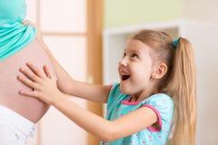 Το ευτυχές κορίτσι παιδιών αγκαλιάζει την έγκυο μητέρα της Στοκ φωτογραφία με δικαίωμα ελεύθερης χρήσης