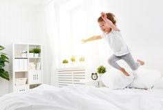 Το ευτυχές κορίτσι παιδιών πηδά και παίζει το κρεβάτι στοκ φωτογραφία