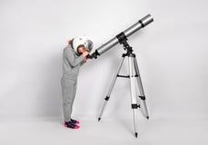 Το ευτυχές κορίτσι παιδιών που ντύνεται σε ένα κοστούμι αστροναυτών κοιτάζει μέσω ενός μεγάλου τηλεσκοπίου Στοκ Εικόνα