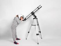 Το ευτυχές κορίτσι παιδιών που ντύνεται σε ένα κοστούμι αστροναυτών κοιτάζει μέσω ενός μεγάλου τηλεσκοπίου Στοκ φωτογραφία με δικαίωμα ελεύθερης χρήσης