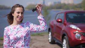 Το ευτυχές κορίτσι παρουσιάζει τα κλειδιά σε ένα νέο αυτοκίνητο, στο υπόβαθρο είναι ένα αυτοκίνητο r απόθεμα βίντεο