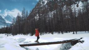 Το ευτυχές κορίτσι περπατά κατά μήκος της γέφυρας στα πλαίσια των χιονοσκεπών βουνών φιλμ μικρού μήκους