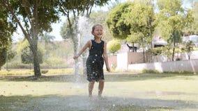 Το ευτυχές κορίτσι πηδά στη λακκούβα κάτω από την προβολή ύδατος στο πάρκο απόθεμα βίντεο
