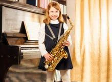 Το ευτυχές κορίτσι στη σχολική στολή κρατά το saxophone alto Στοκ εικόνα με δικαίωμα ελεύθερης χρήσης