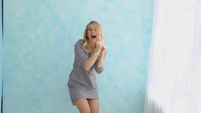 Το ευτυχές κορίτσι στο γκρίζο φόρεμα χορεύει ενάντια σε έναν μπλε τοίχο δίπλα στο παράθυρο φιλμ μικρού μήκους